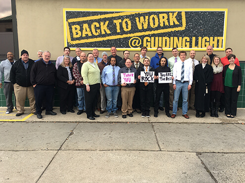 Back to work graduates in front of sign