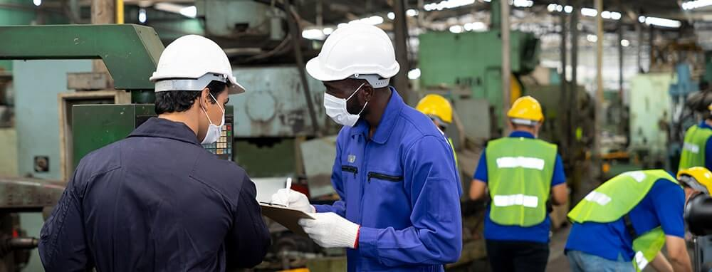 Workers wearing masks in a manufacturing plant