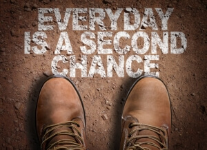 Boots standing on ground next to words that say 'everyday is a second chance'