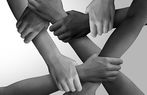 black and white photo of hands and arms crossing and grasping one another