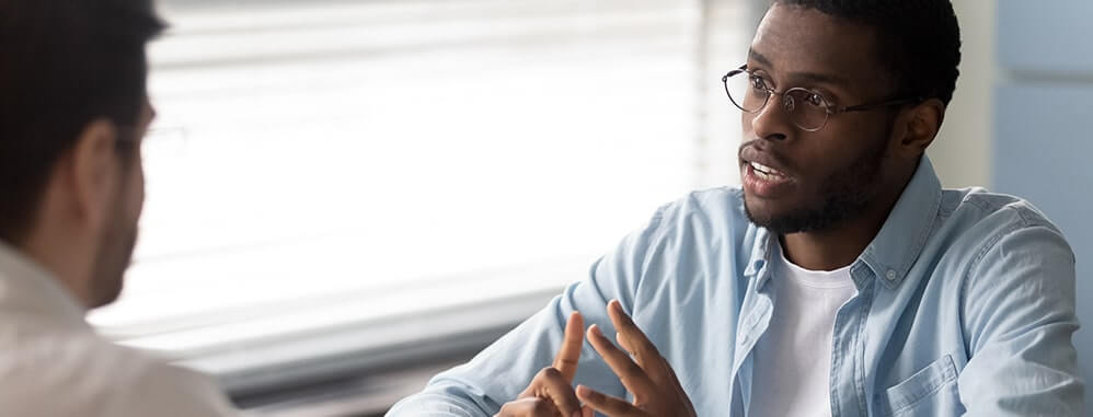 two men discussing job details at a desk