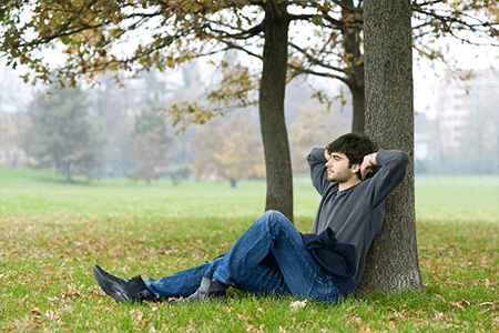 man relaxing, leaning against a tree with his hands behind his head