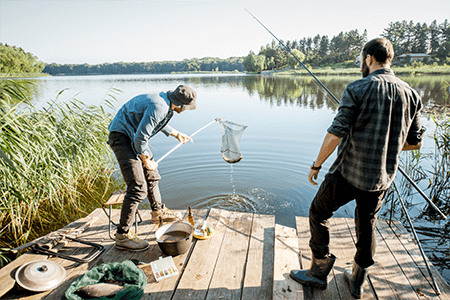 two men on vacation, fishing on a dock, with one holding a net with a fish inside